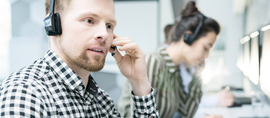 Portrait of  young man wearing headset working with group of help desk operators sitting in row and  talking to clients , copy space